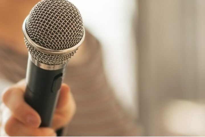 A close up of a microphone being held towards the camera.