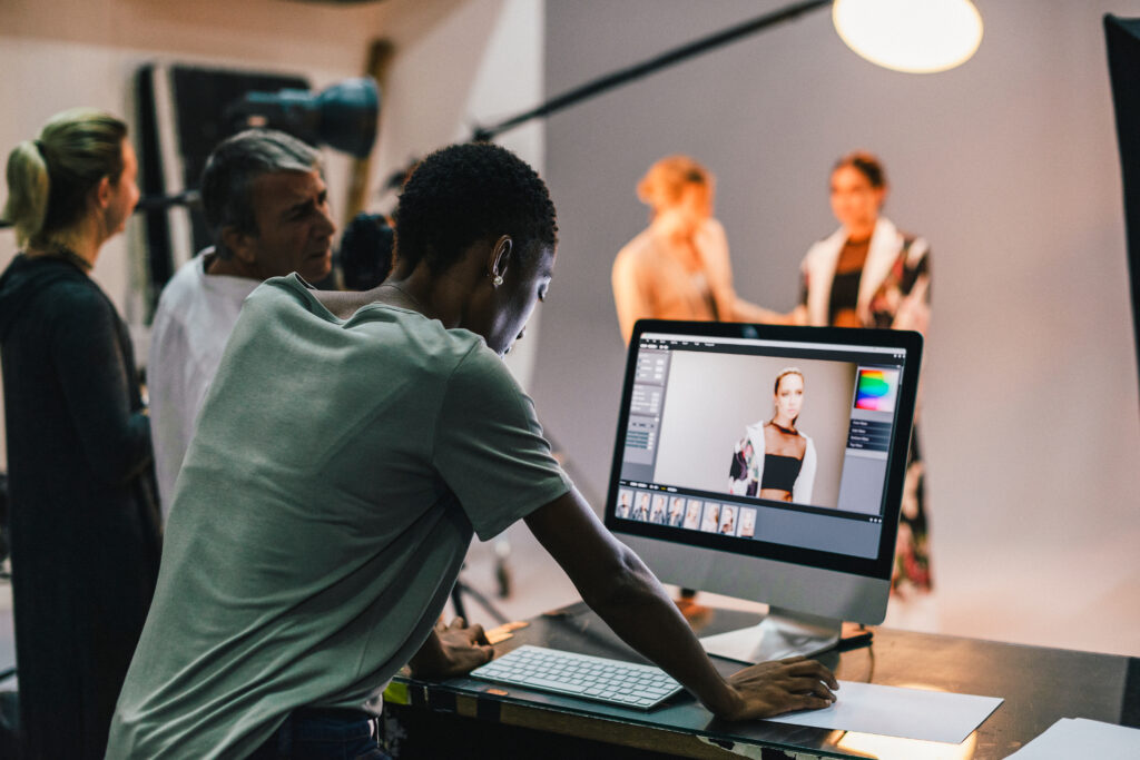 Photograph of a studio photoshoot. A young Black woman edits a photo on a computer screen while colleagues stand nearby. The model and a make up artist are visible but blurred in the background standing on a white photography sheet.